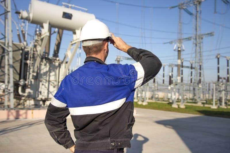 De elektricieningenieur op machts elektrische post bekijkt industrieel materiaal Technicus in helm op elektrohulpkantoor royalty-vrije stock fotografie