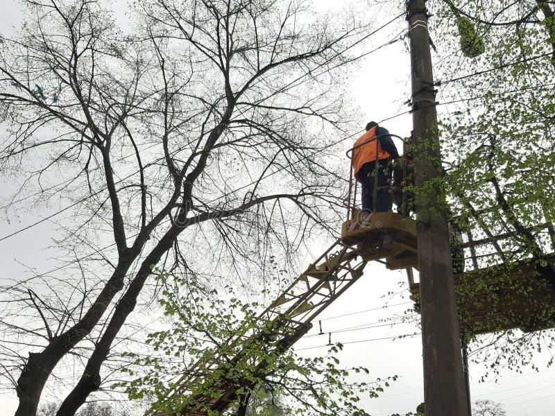 De elektriciens herstellen elektrodraden De arbeiders voeren reparatie van de elektrokring bij een hoogte uit De mensen herstelle stock foto's