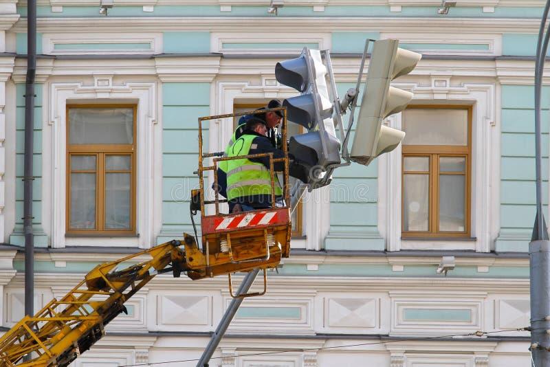 De elektriciens herstellen het verkeerslicht stock fotografie