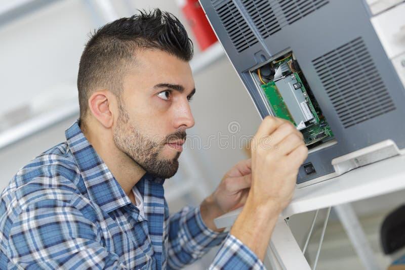 De elektricienwerken met elektronische machine stock afbeelding