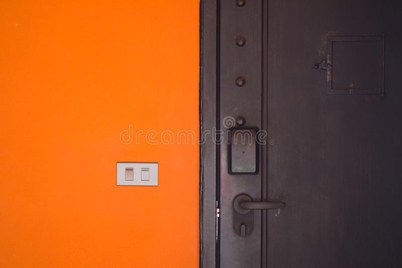 De elektriciteit schakelt oranje cementmuur in stock foto