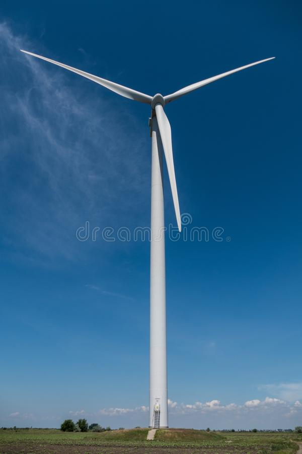 De elektriciteits blauwe hemel van windturbines stock fotografie