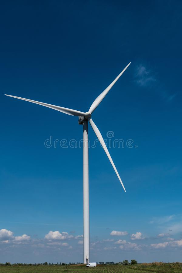 De elektriciteits blauwe hemel van windturbines royalty-vrije stock afbeelding