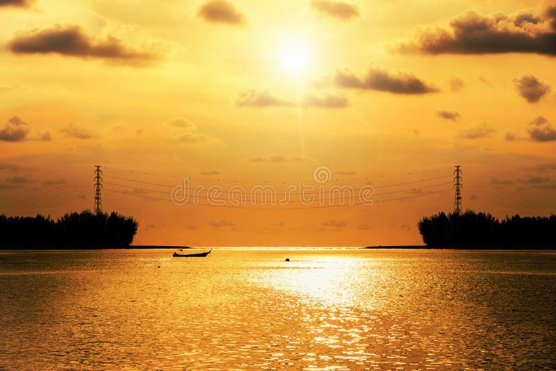 De elektriciteitspyloon van de silhouethoogspanning bij zonsondergang over het overzees royalty-vrije stock fotografie
