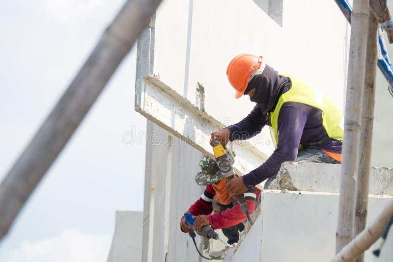 De elektrische boor die van het bouwvakkergebruik concrete muur op bouwgebied boren, Geprefabriceerd huis stock afbeelding
