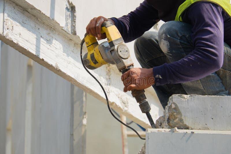 De elektrische boor die van het bouwvakkergebruik concrete muur op bouwgebied boren, Geprefabriceerd huis stock fotografie