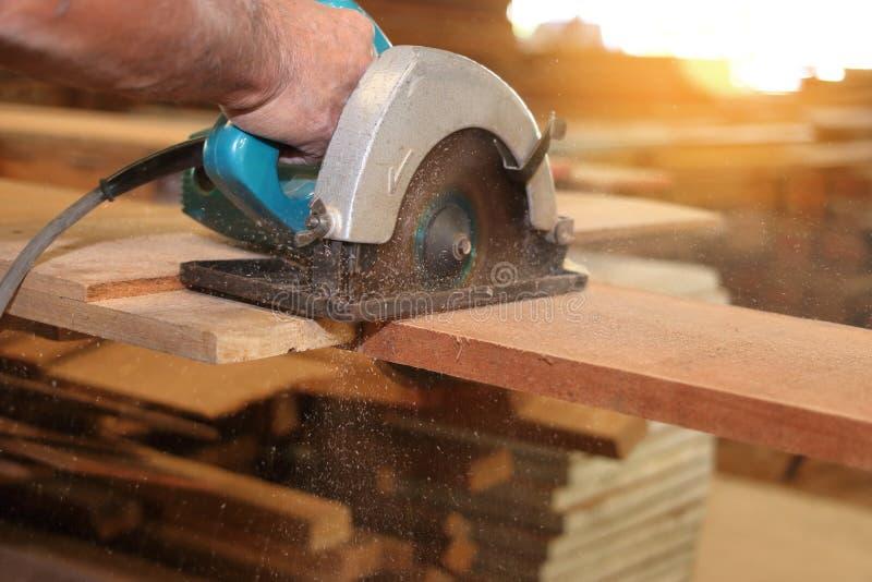 De elektrische cirkelzaag wordt gesneden een stuk van hout door timmerman in timmerwerkworkshop stock afbeeldingen