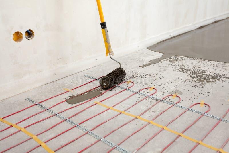De elektrische installatie van het vloer verwarmingssysteem in nieuw huis Close-up van beton, rol en rode elektrodraden stock foto