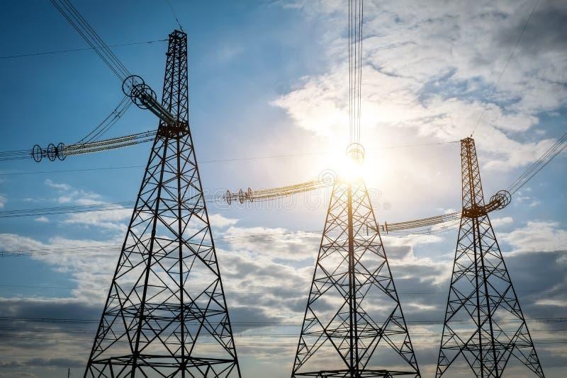 De elektrische torens van de silhouethoogspanning Machtslijnen met hoog voltage De post van de elektriciteitsdistributie royalty-vrije stock fotografie