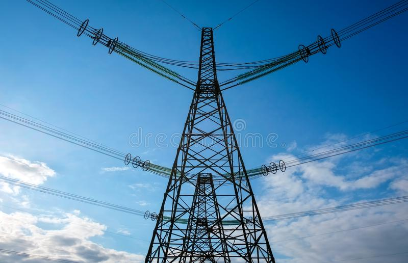 De elektrische torens van de silhouethoogspanning in zonsondergangtijd Machtslijnen met hoog voltage De post van de elektriciteit stock afbeelding