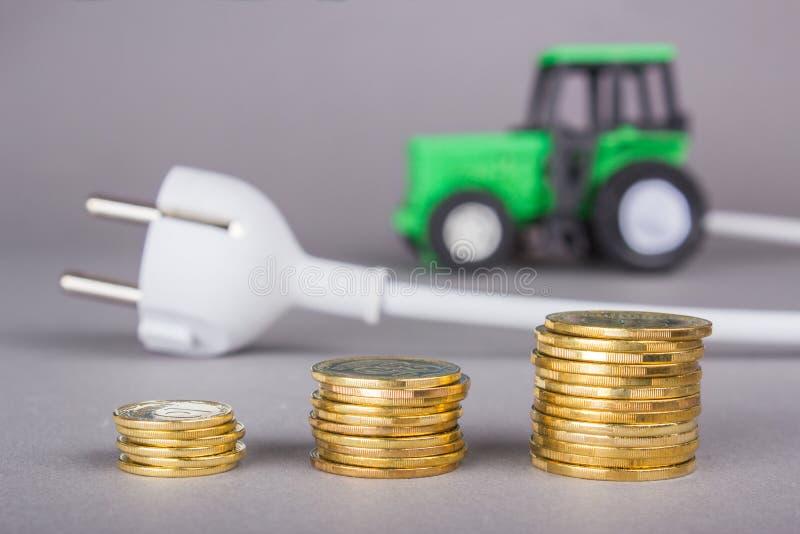 De elektrische tractor wordt geladen van de afzet Ecotech op het landbouwbedrijf Een stapel muntstukken, besparingen stock foto