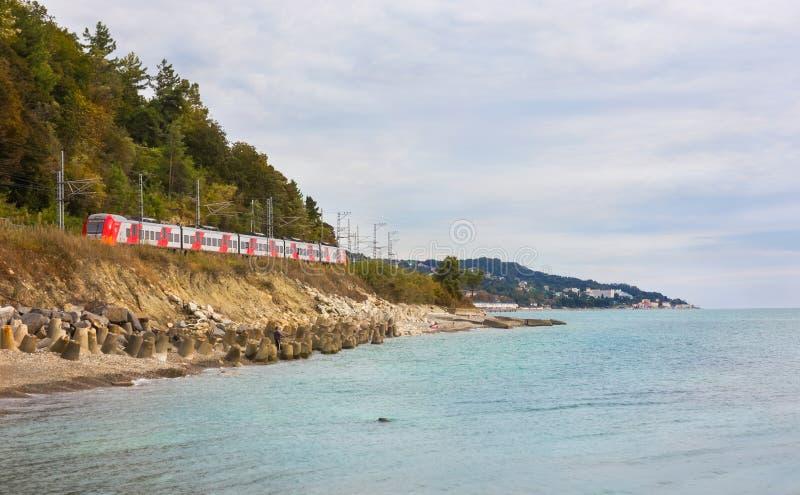 De elektrische trein Lastochka gaat op kust de Zwarte Zee naar Sotchi stock afbeeldingen