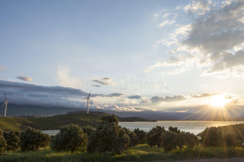 De elektrische turbine van de windgenerator bij de energielandbouwbedrijf van de zonsondergangwind stock afbeeldingen
