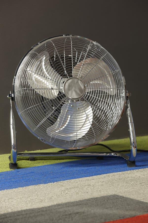 De elektrische ventilator van Chrome over een multicolored tapijt stock afbeelding