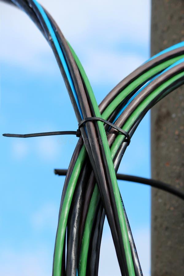 De elektrische zelfstandige geïsoleerde draad is het blauwe, groene en zwarte hangen van de lamppost royalty-vrije stock fotografie