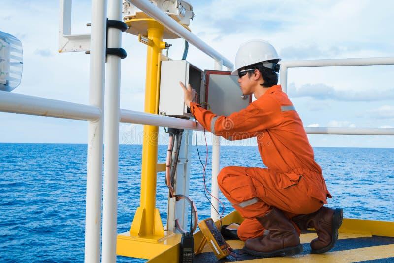 De elektro en Instrumententechnicus is inspectie op verlichting van navigatiesteunregeling bij olie en gasbron ver platform stock afbeelding