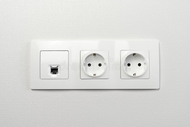 De elektrocontactdozen op de muur met zwarte verbinding Internet stoppen en witte draad Contactdoos met usbkoord en elektriciteit royalty-vrije stock afbeeldingen