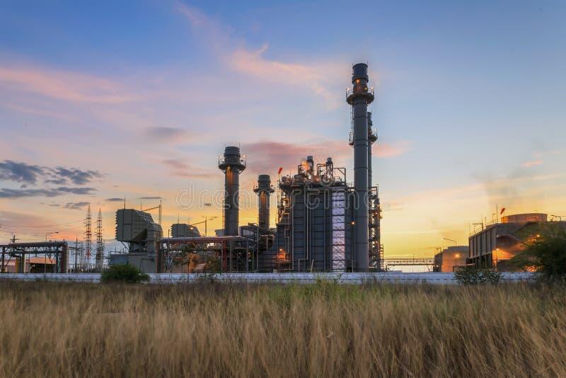 De elektroelektrische centrale van de gasturbine bij schemer met blauwe hemel stock afbeeldingen