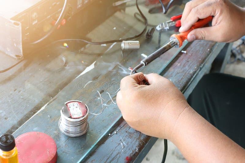 De elektronikatechnicus Men herstelt elektrische apparaten Verbinding van gebroken draden met het solderen van machines royalty-vrije stock afbeeldingen