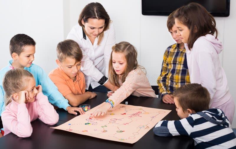 De elementaire leeftijds kalme kinderen bij lijst met raadsspel en dobbelen stock afbeeldingen