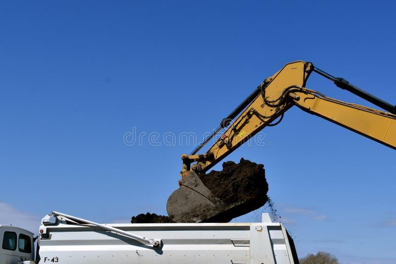 De emmer van backhoe maakt aarde in een vrachtwagendoos leeg stock afbeelding