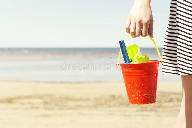 De emmer van de vrouwenholding met het speelgoed van het kinderen` s strand - spade en schop op een zonnige dag stock foto's
