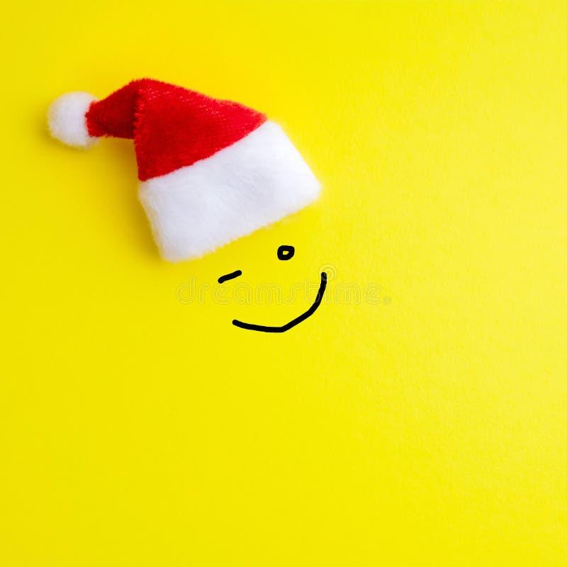 De emotie van vrolijk knipoogt van gezichten op een gele achtergrond onder de rode Santa Claus-hoed worden geschilderd die Concep royalty-vrije stock afbeelding