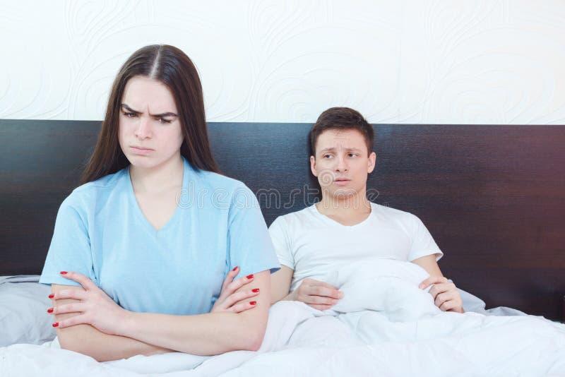 Is de emotioneel gekwetste vrouw boos terwijl man in achtergrondstrijd royalty-vrije stock foto's