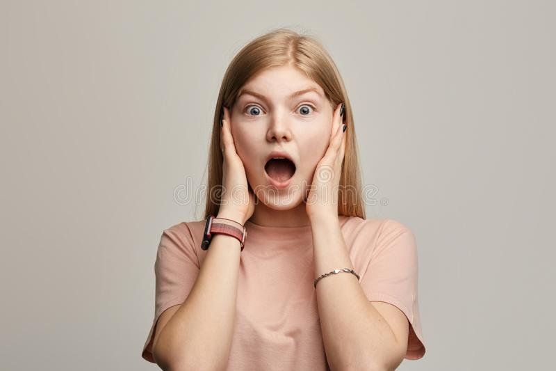 De emotionele doen schrikken vrouw met lang eerlijk haar houdt het sluiten haar oren stock afbeelding