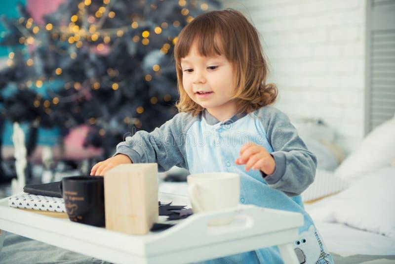 De emotionele het glimlachen meisjezitting in pyjama met Kerstmisgiften dichtbij Nieuwjaar` s boom en het spelen doet escaleren stock afbeeldingen