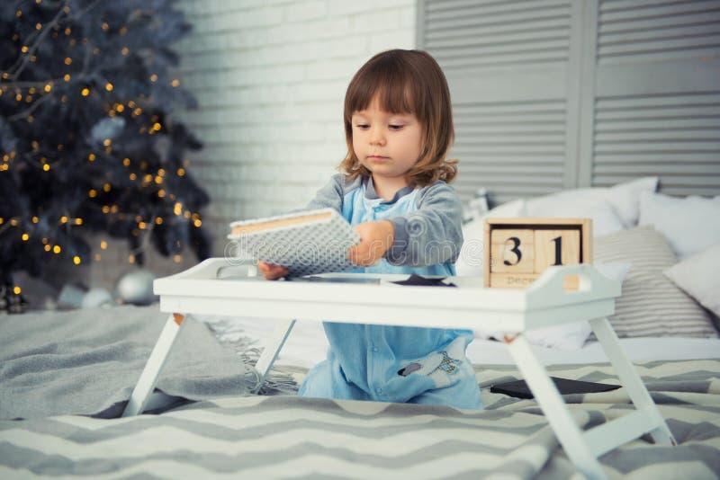 De emotionele het glimlachen meisjezitting in pyjama met Kerstmisgiften dichtbij Nieuwjaar` s boom en het spelen doet escaleren royalty-vrije stock afbeelding