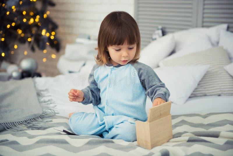 De emotionele het glimlachen meisjezitting in pyjama met Kerstmisgiften dichtbij Nieuwjaar` s boom en het spelen doet escaleren royalty-vrije stock foto's