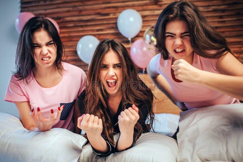 De emotionele jonge vrouwen kijken op camera Zij zitten op bed met boze gezichten De meisjes zijn zeer emotioneel royalty-vrije stock afbeeldingen