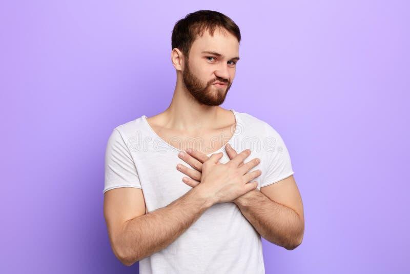 De emotionele knappe jonge mens zet handen op borst stock foto