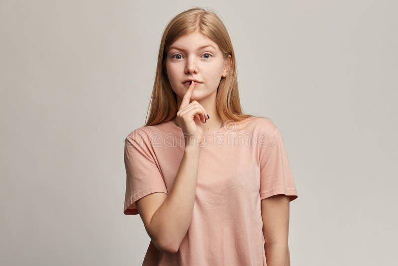 De emotionele mooie vrouw houdt vinger op lippen, toont stiltegebaar, stock afbeeldingen