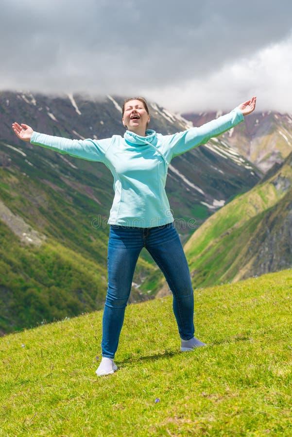 De emotionele vrouw met open wapens in de bergen geniet van stock afbeelding