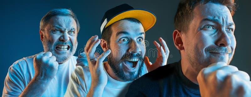 De emotionella ilskna männen som skriker på blå studiobakgrund arkivfoton