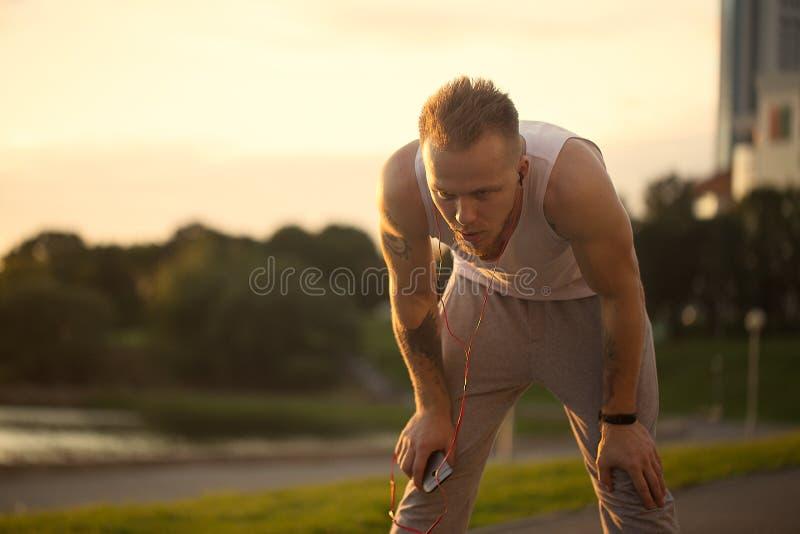 De energieke jonge mens doet oefeningen en runnig met telefoon en m royalty-vrije stock afbeelding