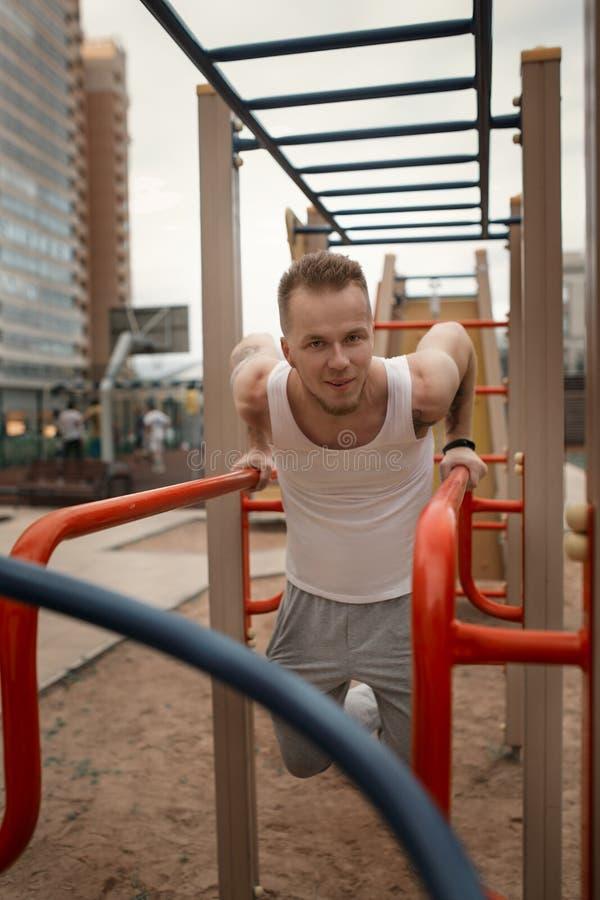 De energieke jonge mens doet in openlucht oefeningen in sportvierkant aan kee royalty-vrije stock fotografie