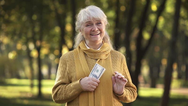 De energieke oude stapel van de dameholding dollarrekeningen in park, geplande pensionering royalty-vrije stock foto