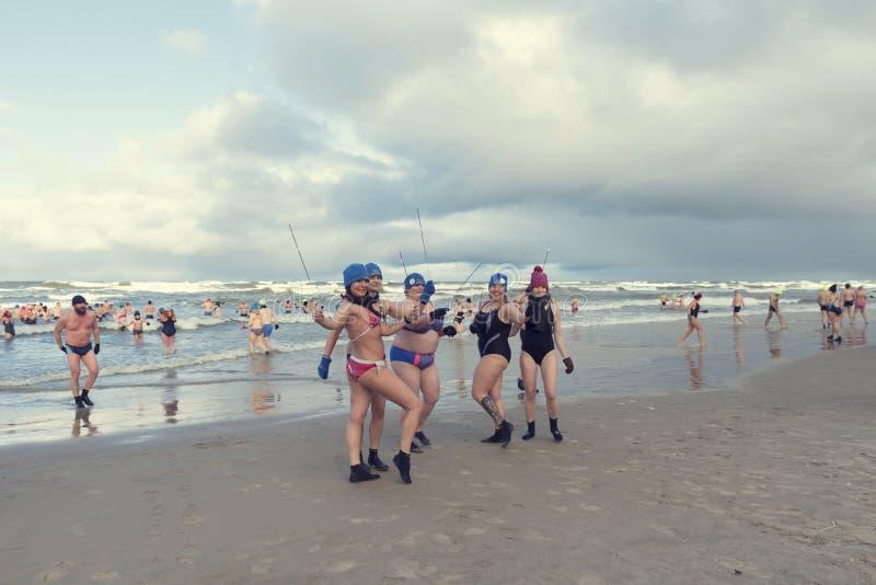 5 de enero de 2019, Stegna, Polonia Gente que nada en el mar durante el invierno Cinco señoras que presentan con las bengalas fotos de archivo