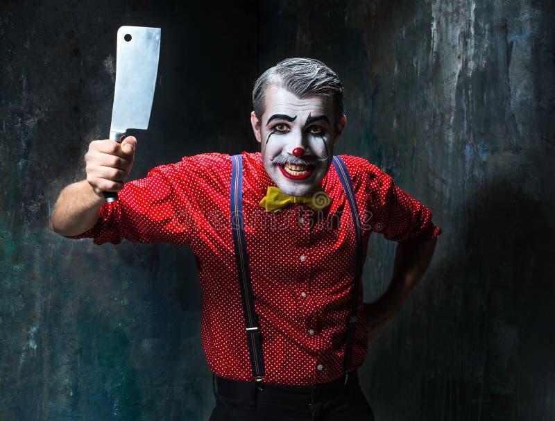 De enge clown die een mes op dack houden Het concept van Halloween stock afbeelding