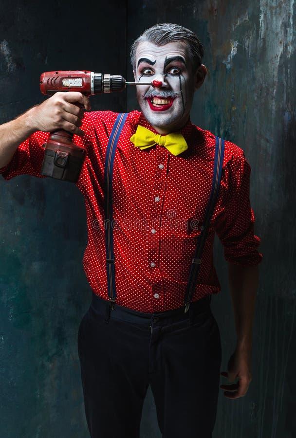 De enge clown en de elektrische boor op dackachtergrond Het concept van Halloween stock foto