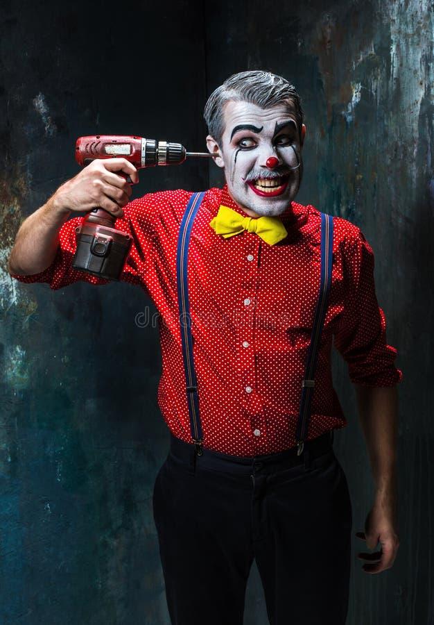 De enge clown en de elektrische boor op dackachtergrond Het concept van Halloween royalty-vrije stock fotografie