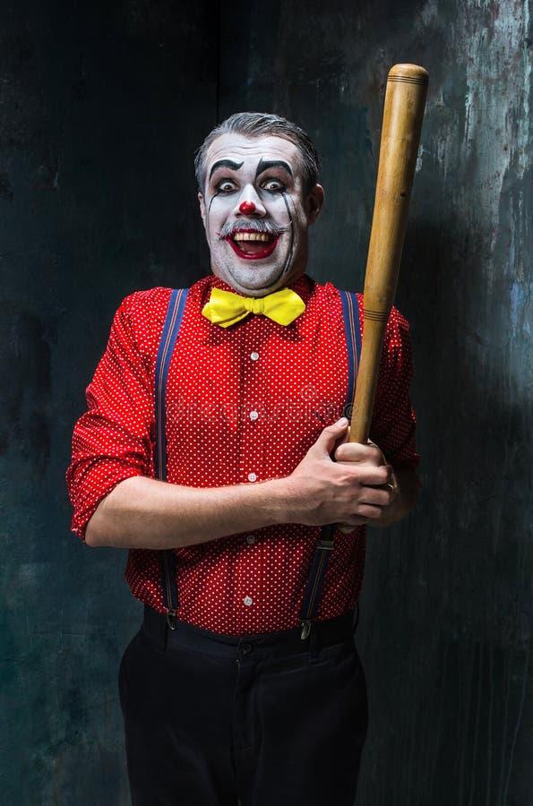 De enge clown en de honkbal-knuppel op dackachtergrond Het concept van Halloween royalty-vrije stock foto