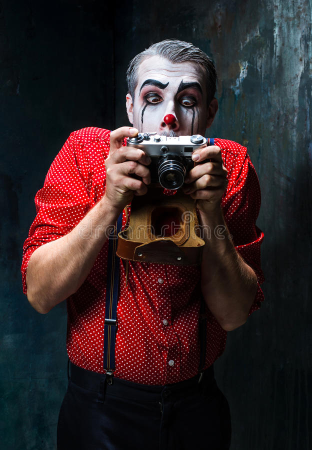 De enge clown en een camera op dackachtergrond Het concept van Halloween royalty-vrije stock afbeelding