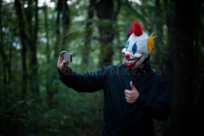 De enge clown neemt selfie met smartphone in hout stock fotografie