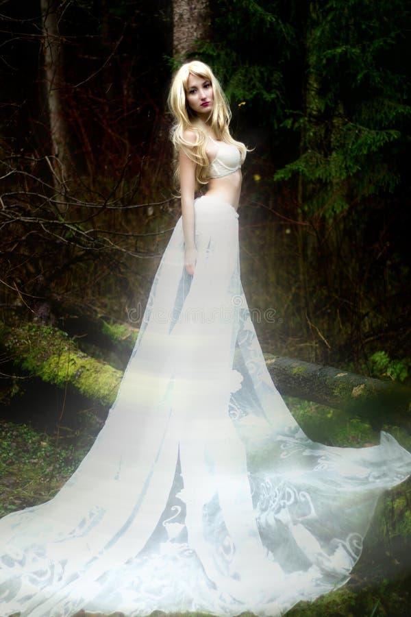 De engel van de blondebruid in lange witte rok die zich in donker bos bevinden stock foto