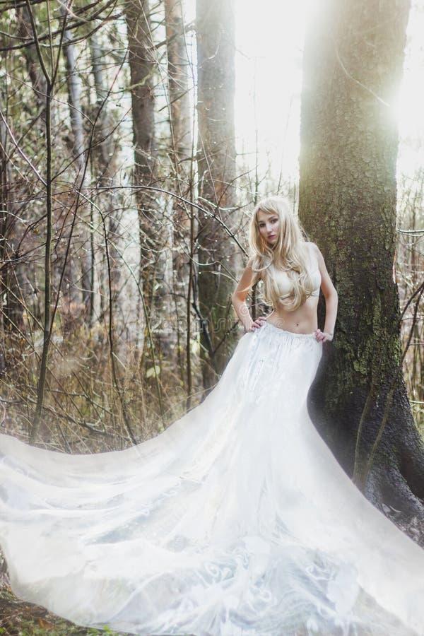De engel van de blondebruid in lange witte rok die zich in zonnig bos bevinden stock fotografie