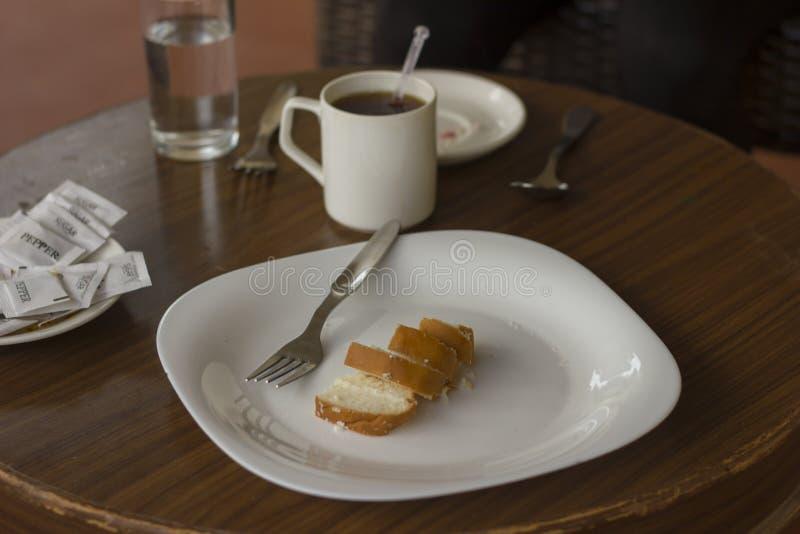 De Engelse theecake diende met hete kop thee in een openluchttuinkoffie in een witte ceramische plaat stock foto